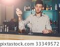 Young bartender mixing cosmopolitan cocktail 33349572