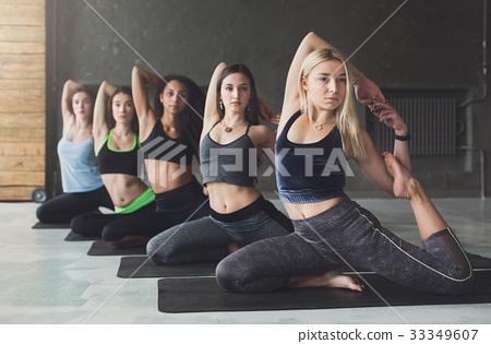 Young women in yoga class, mermaid pose stretching 33349607
