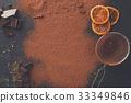 Cocoa powder in a sieve over black slate 33349846