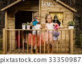 Two girls play with watering can in a tree house 33350987