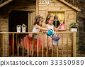 Two girls play with watering can in a tree house 33350989