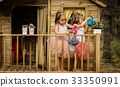 Two girls play with watering can in a tree house 33350991
