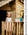 lovely girl play with watering can in a tree house 33351010