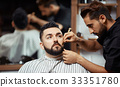 Concentrated barber working with man 33351780