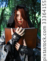 Portrait of witch in cloak with book 33364155
