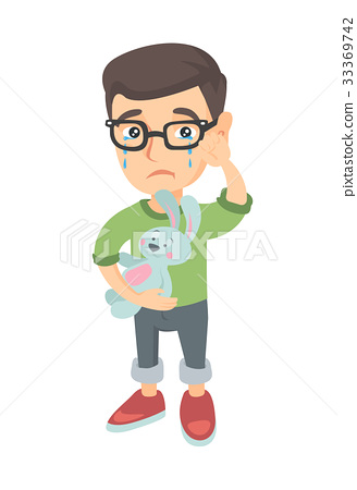 Caucasian boy in glasses crying and holding toy. 33369742