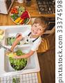 Little boy washes vegetables before eating 33374598