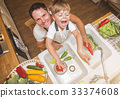 Father with son washes vegetables before eating 33374608