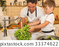 Father with son washes vegetables before eating 33374622