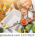Father with son washes vegetables before eating 33374625