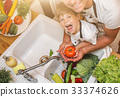 Father with son washes vegetables before eating 33374626
