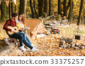 autumn picnic. Happy couple with guitar near the 33375257