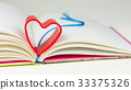 Red heart over diary book with bookmark on white 33375326