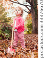 Happy toddler girl playing in the fall leaves  33376670