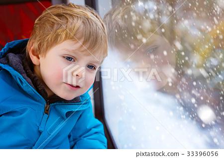Cute little toddler boy looking out train window 33396056