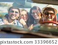 Group of cheerful young friends driving car and 33396652