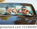 Group of cheerful young friends driving car and 33396689