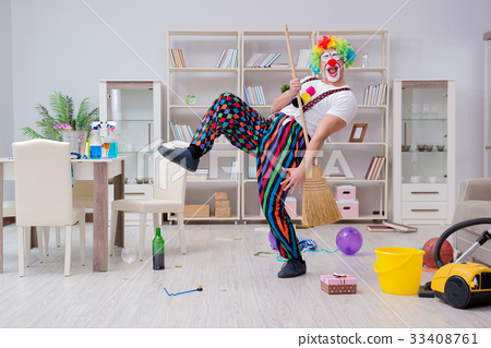 Funny clown doing cleaning at home 33408761