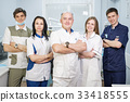 Group of dentists standing in their office and 33418555