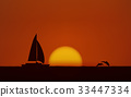 Silhouette jumping dolphin and sailboat in sea 33447334