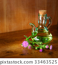 Oil and flowers of milk thistle on wooden 33463525