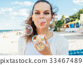 Young woman blow bubbles on the beach 33467489