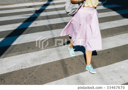 Girl in a pink skirt and sneakers crossing road 33467670