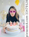 bautiful caucasian girl blowing candles  her cake 33479328