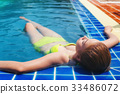 Beautiful girl relaxing in the pool her vacation. 33486072