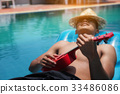 The young man relaxes and plays Ukulele on rubber 33486086