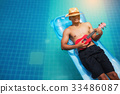The young man relaxes and plays Ukulele on rubber 33486087