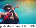 The young man relaxes and plays Ukulele on rubber 33486092