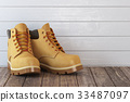 Yellow boots on a wooden table 33487097