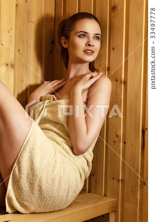 Beautiful red-haired woman relaxing in a finish sauna 33497778