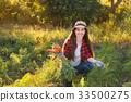 gardener with carrots in a vegetable garden 33500275