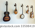 Ancient stringed musical instruments on wall. 33506419