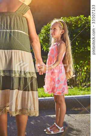 Child with grandmother holding hands. 33507133
