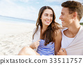 Romantic young couple sitting on the beach 33511757