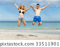 Happy couple jumping on beach vacations 33511901