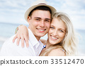 Romantic young couple sitting on the beach 33512470