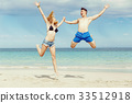 Happy couple jumping on beach vacations 33512918