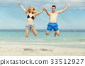 Happy couple jumping on beach vacations 33512927