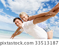 Happy couple jumping on beach vacations 33513187
