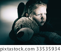Sad little girl embracing her teddy bear 33535934