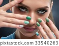 Brunette woman with shiny manicure and green 33540263
