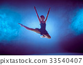 Beautiful young ballet dancer jumping on a lilac 33540407