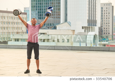 Young man holding two hoverboards. 33540706