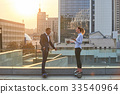 Businessman and woman, city background. 33540964