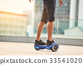 Legs of guy riding hoverboard. 33541020