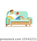 Young man lying on a light blue sofa and reading a 33542221